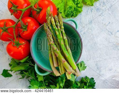 Empty Saucepan, Asparagus, Tomato, Herbs On Concrete Background