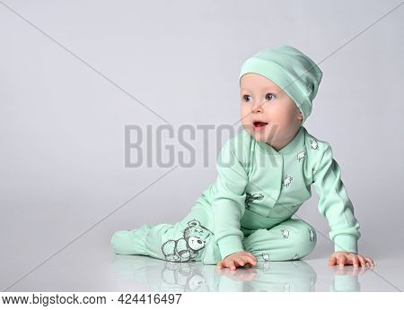 Joyful Baby Infant Toddler Sits In A Cotton Jumpsuit And A Matching Cap And Looks Into The Corner Of