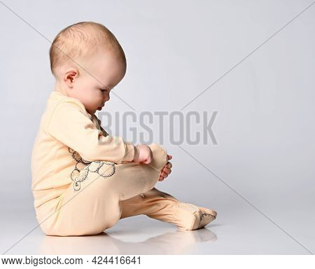 Little Toddler Toddler Child Examines His Leg With Interest In A Yellow Cotton Jumpsuit For Toddlers