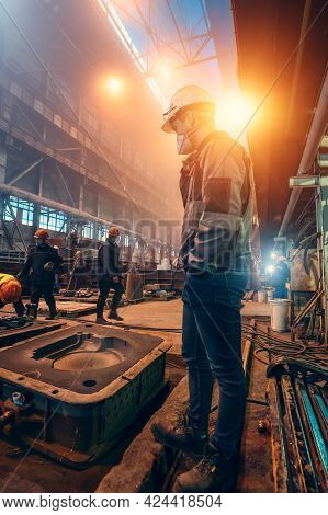Workers In Uniforms, Helmets And Protective Face Masks In The Metallurgical Plant Shop. Steel Produc