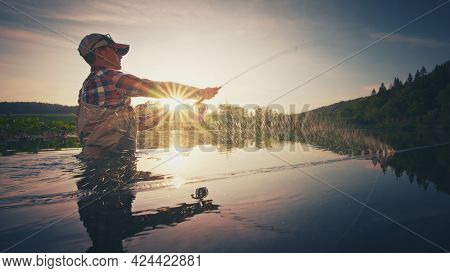Fly fisherman stands in the water and casts the fly with fishing rod using Roll Cast with lot of splashes