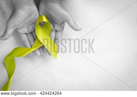 Hands Holding Light Lime Green Ribbon On White Fabric Background With Copy Space. World Mental Healt
