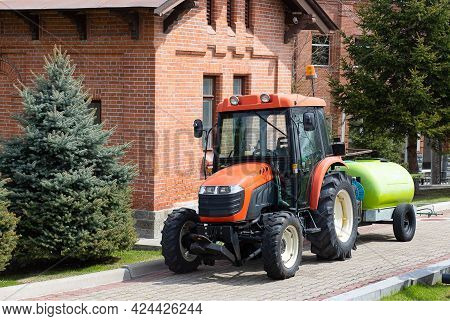 Tractor With Water Tank Trailer In The Park On A Sunny Summer Day. Minitractor For Lawn Watering. Fr