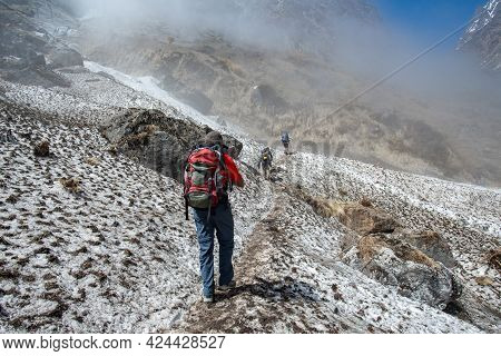 Group Of Trekkers Walking On The Snowfield After Avalanche In Annapurna Sanctuary Of Nepal. Annapurn