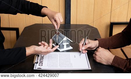 A Real Estate Agent Broker Hand Over The House Key To The New Owner After Completing The Signing Acc