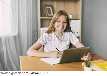 Portrait Of A Smiling Girl Taking Notes While Preparing For The Exam Using A Tablet. The Concept Of