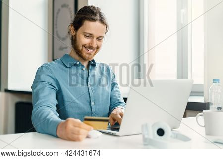 Happy Young Man Sitting At Desk In Office With Credit Card And Shopping Online On Laptop, Joyful Mal