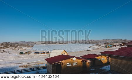 Tourist Base On The Shore Of A Frozen Lake. Single-storey Wooden Houses With Double-glazed Windows,