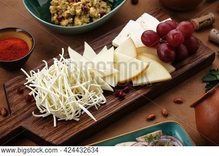 Assorted Caucasian Cheeses Are Neatly Laid Out On A Wooden Board. Cheese Plate In A Georgian Restaur