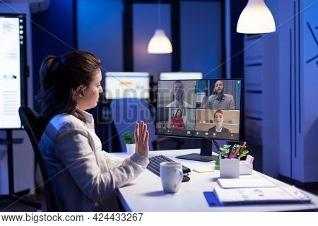 Back View Of Business Woman Talking About Sale Report In Video Conference Working Overtime In Start-
