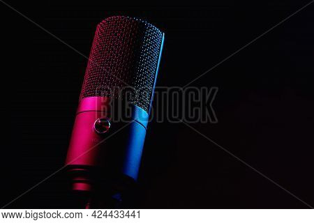 Studio Microphone On Dark Background With Copy Space. Black Professional Condencer Microphone With N
