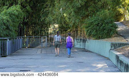 Mackay, Queensland, Australia - June 2021: Two Women Friends Walking In The Botanic Gardens For Thei