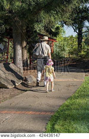 Mackay, Queensland, Australia - June 2021: A Grandfather Carrying Bags Walks With His Little Grandda