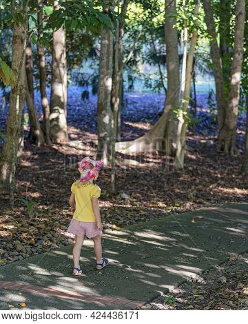 Mackay, Queensland, Australia - June 2021: A Young Caucasian Child In Shorts And A Pink Hat Strolls