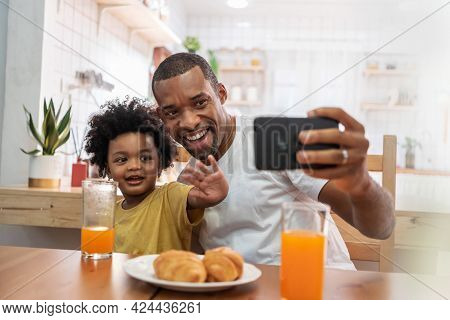 Happy Smiling African American Father And Little Son Doing Video Call With Smartphone And Waving Han