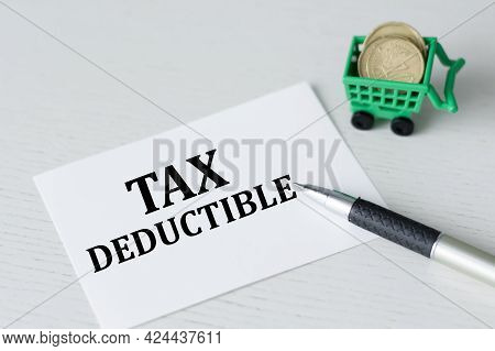 A Card With Text Tax Deductible On The Table Next To A Pen And A Basket With Manet, Business Concept