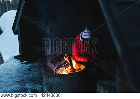 Woman sitting by the bonfire in her log cabin