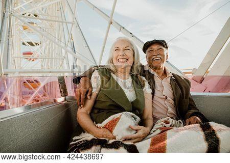 Cheerful senior couple enjoying a Ferris wheel by the Santa Monica pier