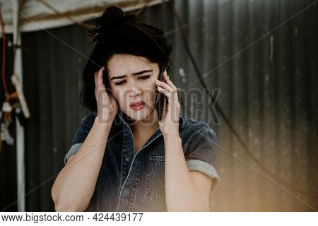 Female carpenter talking on a phone with worries