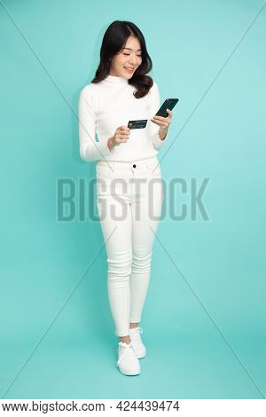 Young Asian Woman Using Mobile Phone And Holding Credit Card To Paying Of Shopping Application Or Pa