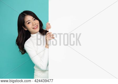 Cheerful Young Asian Woman Is Standing Behind The White Blank Banner Or Empty Copy Space Advertiseme