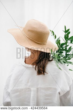 Woman wearing a woven hat carrying eucalyptus leaves