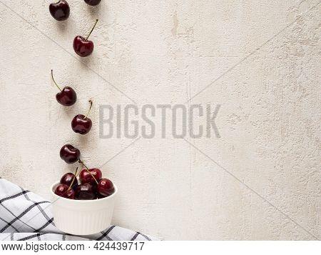 Red Cherries Falling Into A White Ramekin