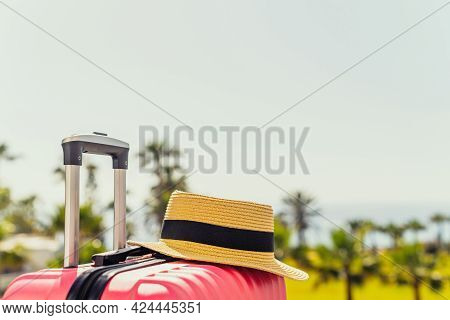 Pink Suitcase And Beach Hat Standing On Passengers Ladder Of Airplane Opposite Sea Coastline With Pa