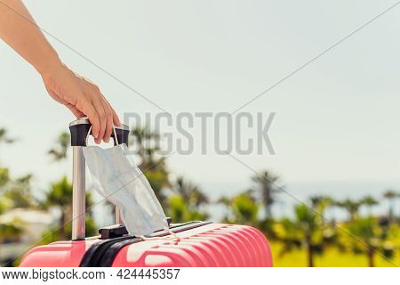 Woman With Pink Suitcase, Protective Mask Standing On Passengers Ladder And Getting Out Of Airplane