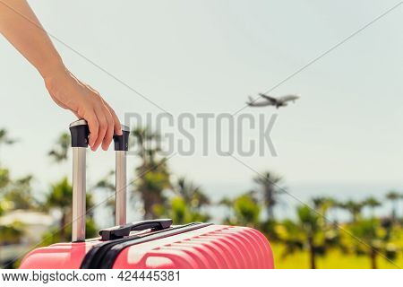 Woman With Pink Suitcase Standing On Passengers Ladder And Getting Out Of Airplane Opposite Sea Coas