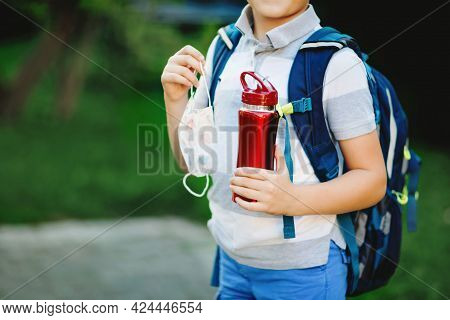 Closeup Of Kid Boy, Medical Mask, Water Bottle And Backpack Or Satchel. Schoolkid On Way To School.