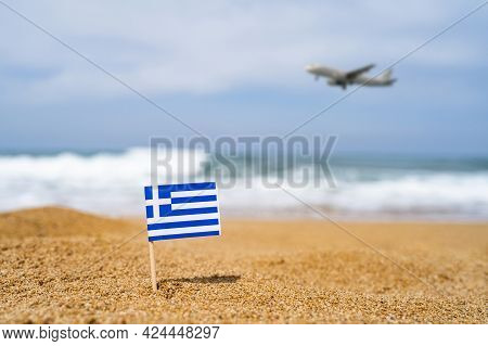 Flag Of Greece In The Form Of A Toothpick In The Sand Of Beach Opposite Sea Wave With Landing Airpla