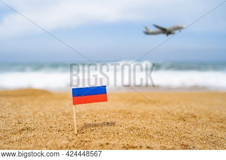 Flag Of Russia In The Form Of A Toothpick In The Sand Of Beach Opposite Sea Wave With Landing Airpla