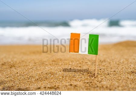 Flag Of Ireland In The Form Of A Toothpick In The Sand Of Beach Opposite Sea Wave. Travel Concept.