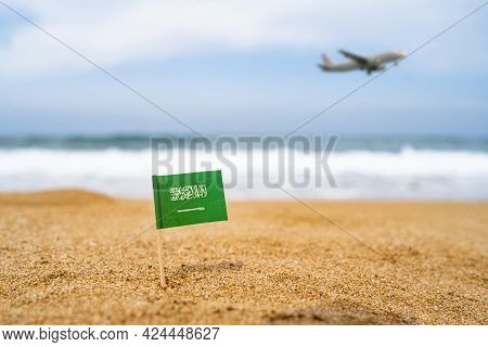 Flag Of Saudi Arabia In The Form Of A Toothpick In The Sand Of Beach Opposite Sea Wave With Landing