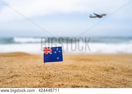 Flag Of New Zealand In The Form Of A Toothpick In The Sand Of Beach Opposite Sea Wave With Landing A