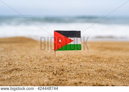 Flag Of Jordan In The Form Of A Toothpick In The Sand Of Beach Opposite Sea Wave. Travel Concept