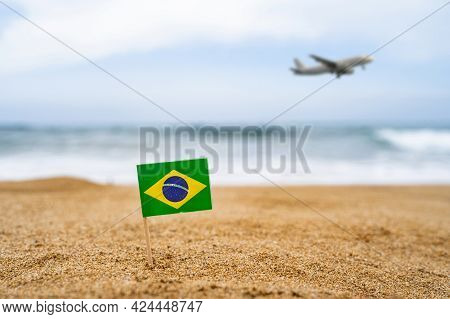 Flag Of Brazil In The Form Of A Toothpick In The Sand Of Beach Opposite Sea Wave With Landing Airpla