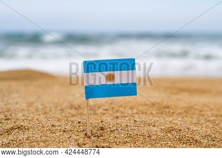 Flag Of Argentina In The Form Of A Toothpick In The Sand Of Beach Opposite Sea Wave. Travel Concept