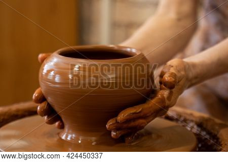 Old Woman Potter Working On Potter Wheel Making A Clay Pot. Master Forming The Clay With Her Hands C