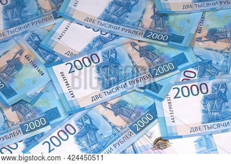 Background Of Banknotes Of Two Thousand Russian Rubles In A Blue Design Laying On A Surface