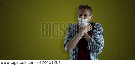 A Male Person Holding A Throat While Choking And Can Not Breathe, Isolated Against The Wall, Coronav