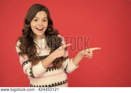 This Way. Direction Indicator. Happy Girl Pointing At Red Background Copy Space. Little Kid With Poi