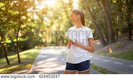 Woman Putting On Earphones To Listen Music Before Jogging Summer Park Caucasian Female Preparing To