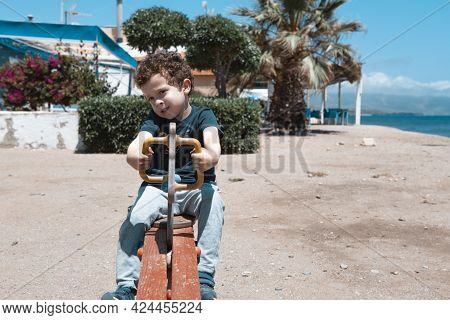 Small 4-5 Year Old Caucasian-looking Boy With Curly Hair Riding On A Seesaw On The Beach Small 4-5 Y