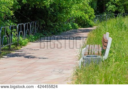 On A Summer Afternoon, An Empty Park Bench Sits Along A Cobbled Footpath Among Lush Green Vegetation