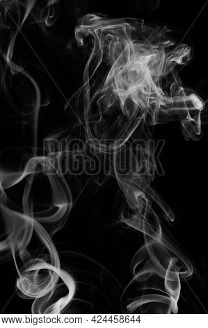 White Smoke Swirls On Black Background