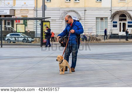 Kharkov, Ukraine - April 5, 2021: Young Man With Labrador Puppy Walking On Constitution Square In Kh