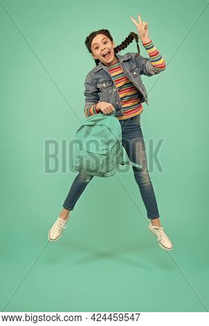 Adding A Joy To Your Holidays. Happy Girl Jump Blue Background. Little Child Make Victory Sign In Mi