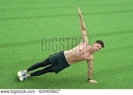 Strong Young Man Doing Sports Outdoors. Man Practicing Yoga On Grass. Working Out In Fitness Gym. Do